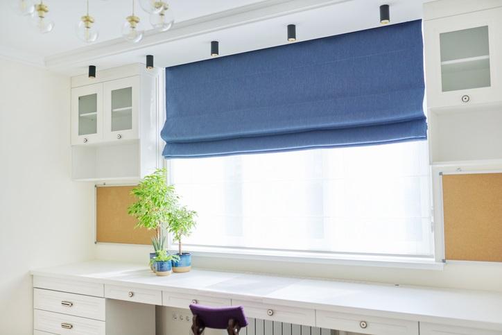 Interior of the room, workplace near window, light furniture, desk, blue roman blind, wall shelves.