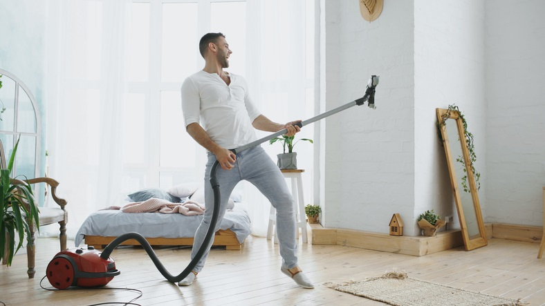 Man jams out as he vacuums because his music is following him from room to room