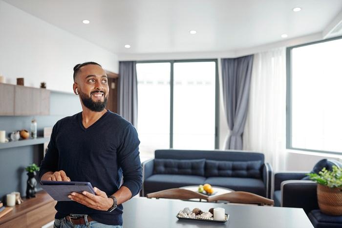 Bearded man using smart home application on digital tablet.