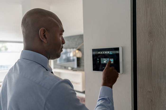 Man locking the door of a house using a home automation system.