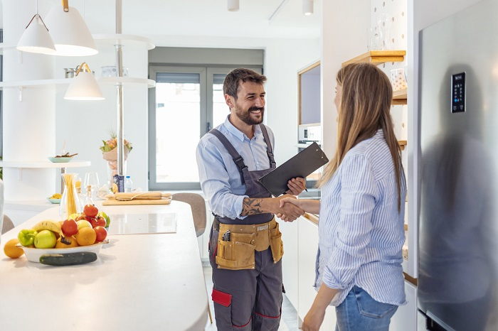 Service worker shaking hands with a woman in a modern kitchen.
