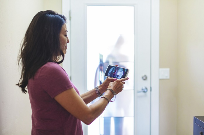 Woman checks tablet to see who is at her front door.