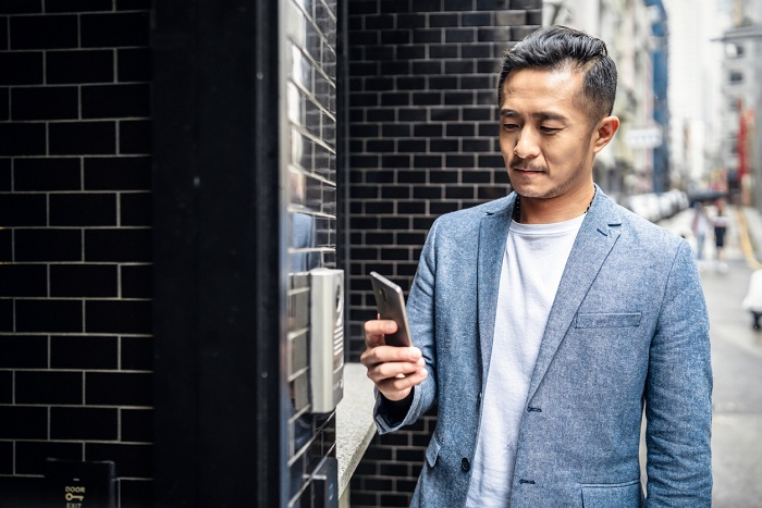Man checks app on smart phone to enter building.