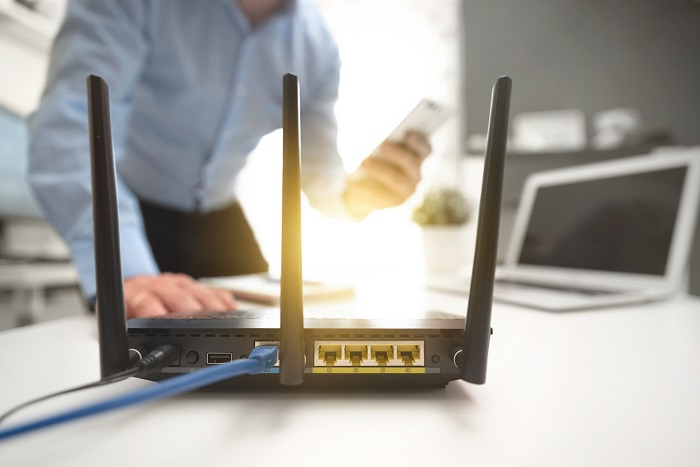 Wireless internet router with man working in the background.