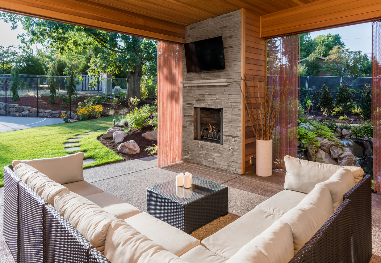 Covered patio with fireplace, TV, and couch