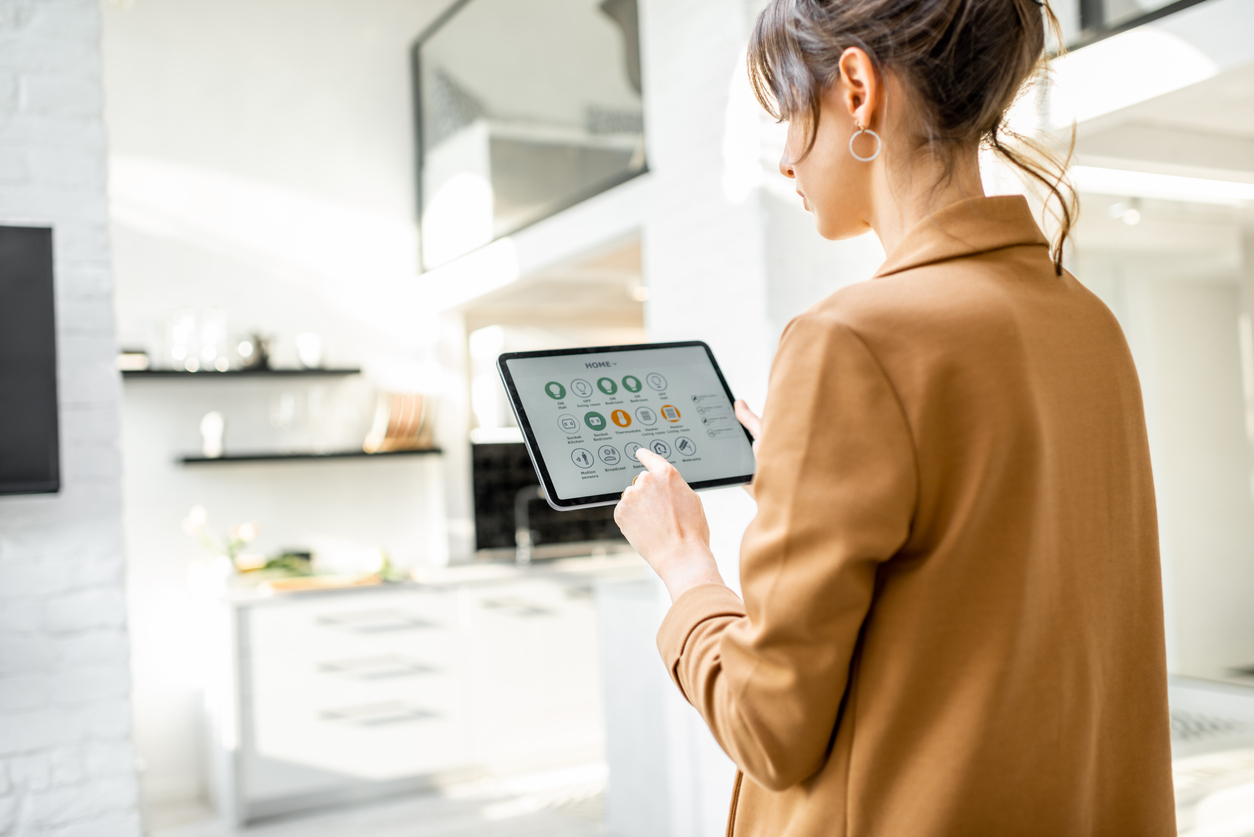 Woman uses smart home tablet controller at home