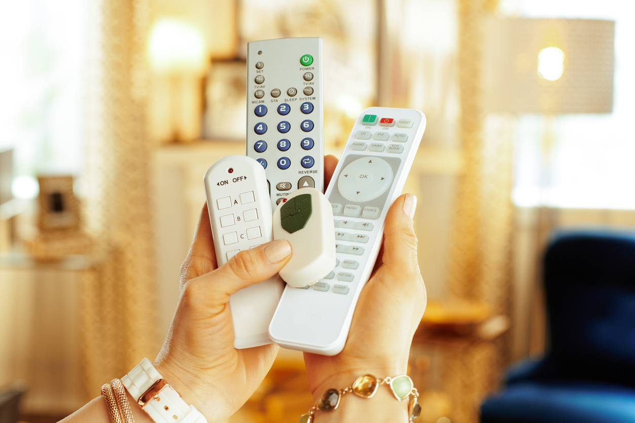 hand holding four various remote controls
