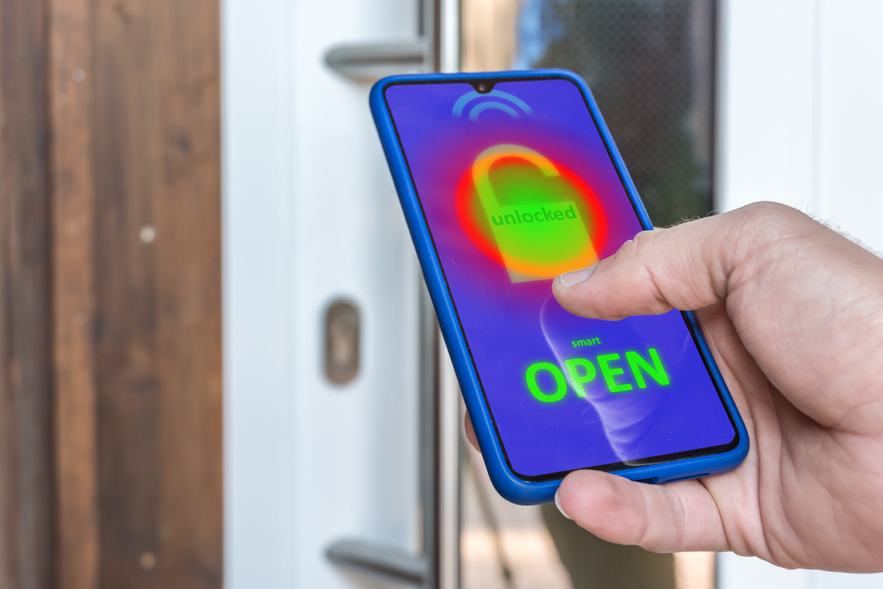 Hand holding a smart phone which is unlocking the smart lock on a front door