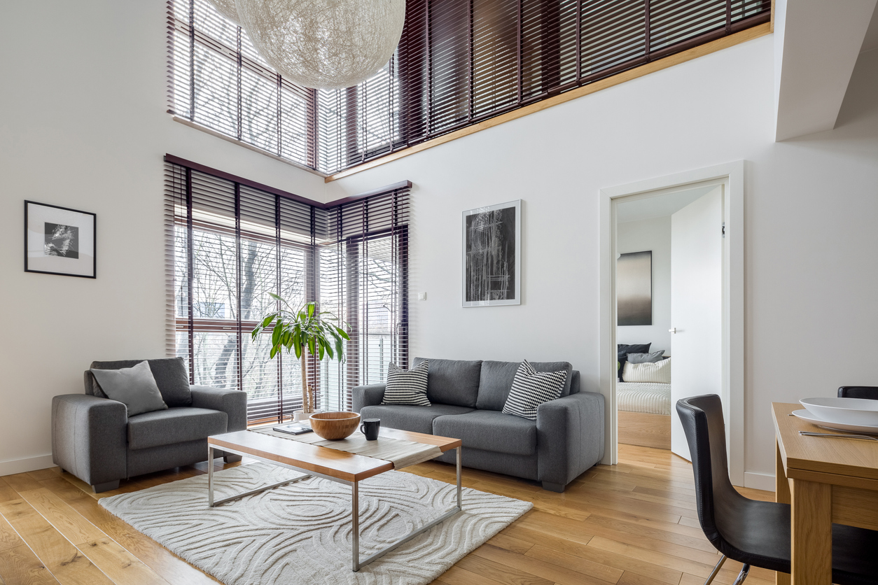 Living room with many, big windows with smart blinds and hardwood floor