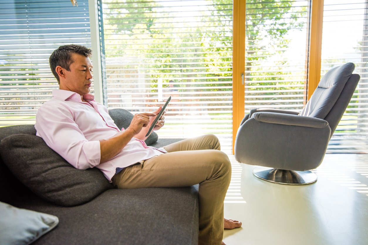 man controlling smart blinds with digital tablet