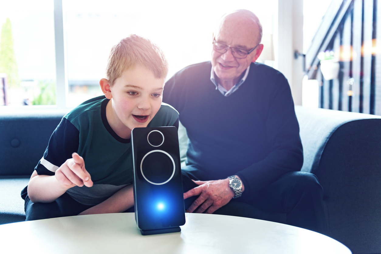 A boy and his grandfather voice control a digital assistant in their living room