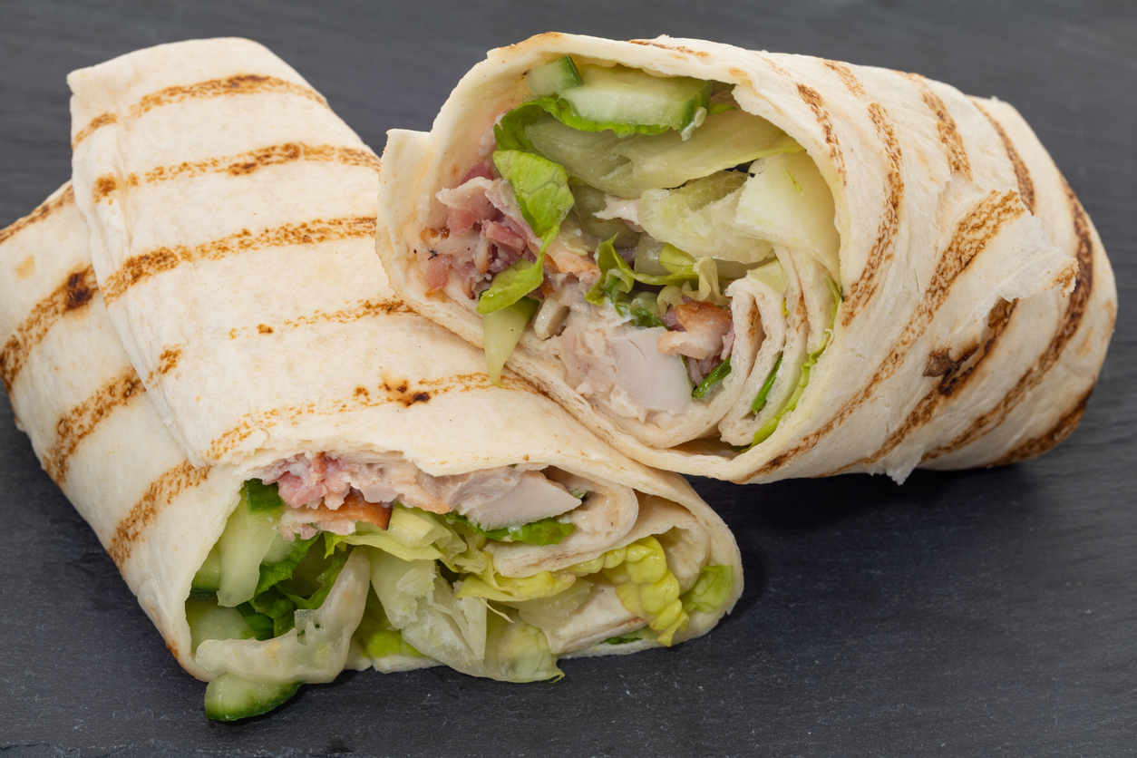 chicken, bacon, and salad wrap placed on a slate