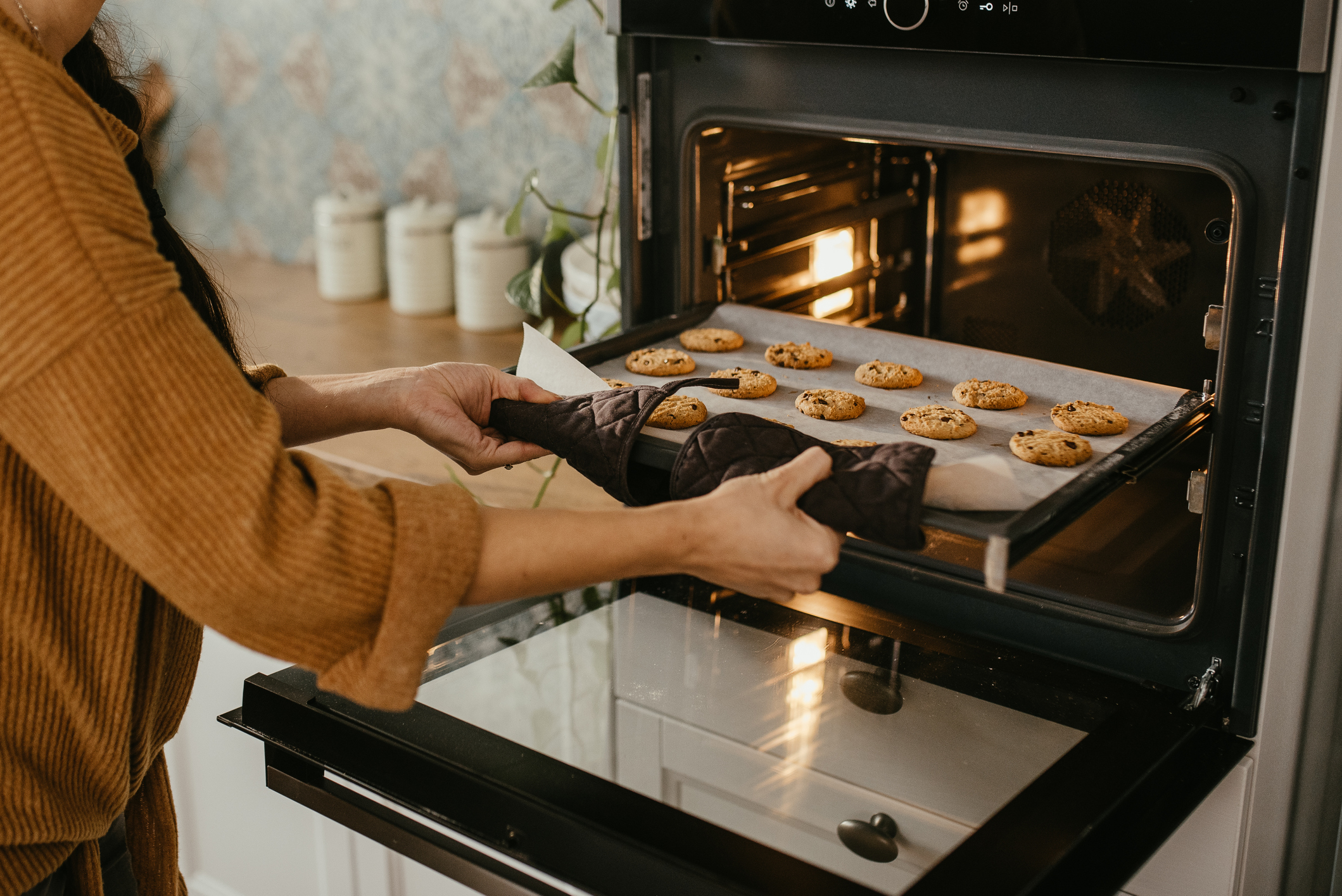 pulling a tray of cookies out of a wall oven