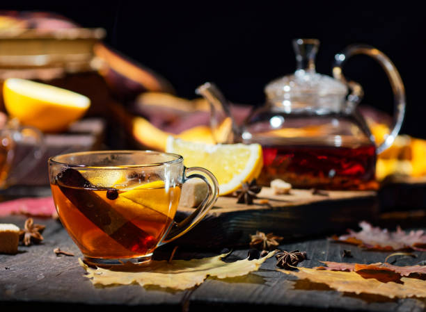 glass teacup of tea with cinnamon and tea with fall décor and teapot