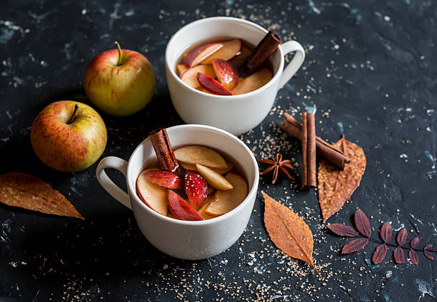 two cups of apple cider with apples, cinnamon, and cloves on the table