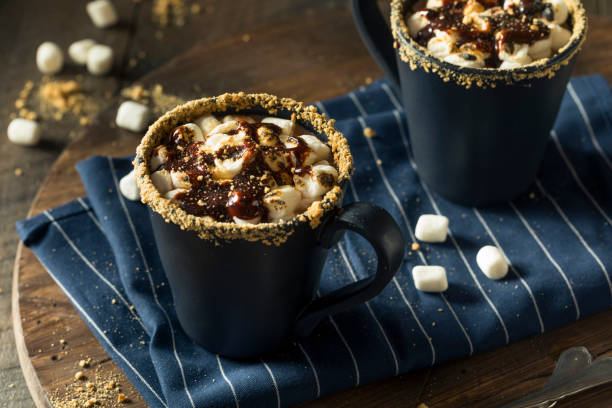 two hot chocolate filled mugs with graham cracker rims