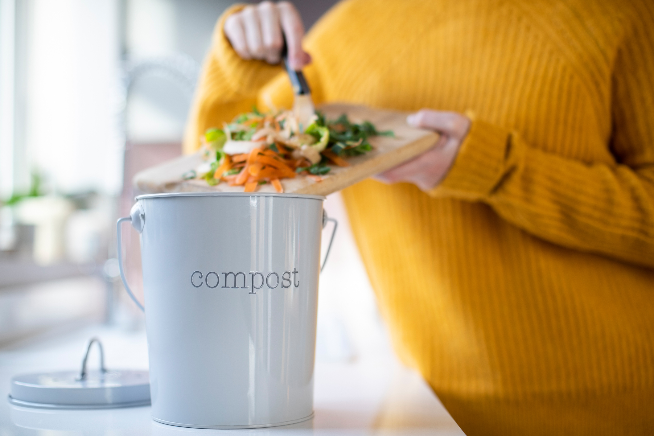 disposing of food waste into compost bin