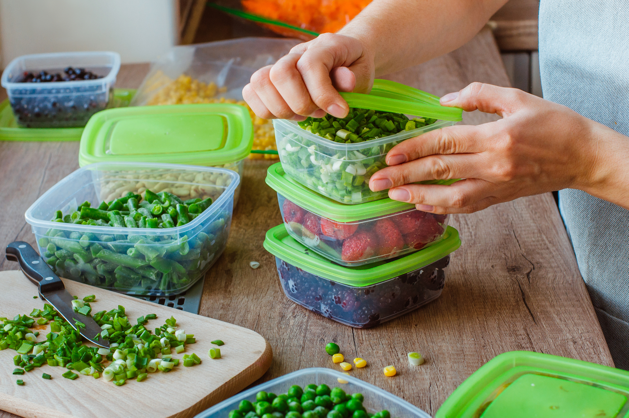 adding food to storage containers for meal prep