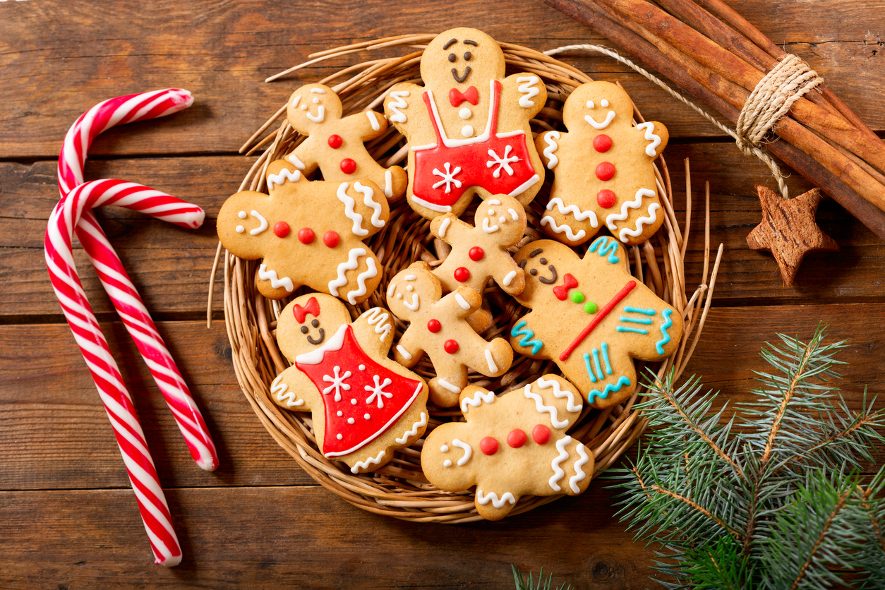 decorated gingerbread cookies on a wicker platter with candy canes, cinnamon and a Spruce sprig as decoration