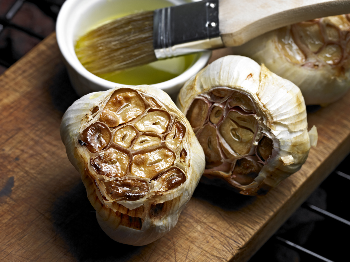 oven roasted garlic heads on a wooden platter with olive oil and pastry brush