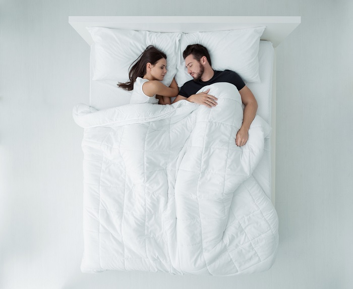 Couple relaxing and sleeping in bed.