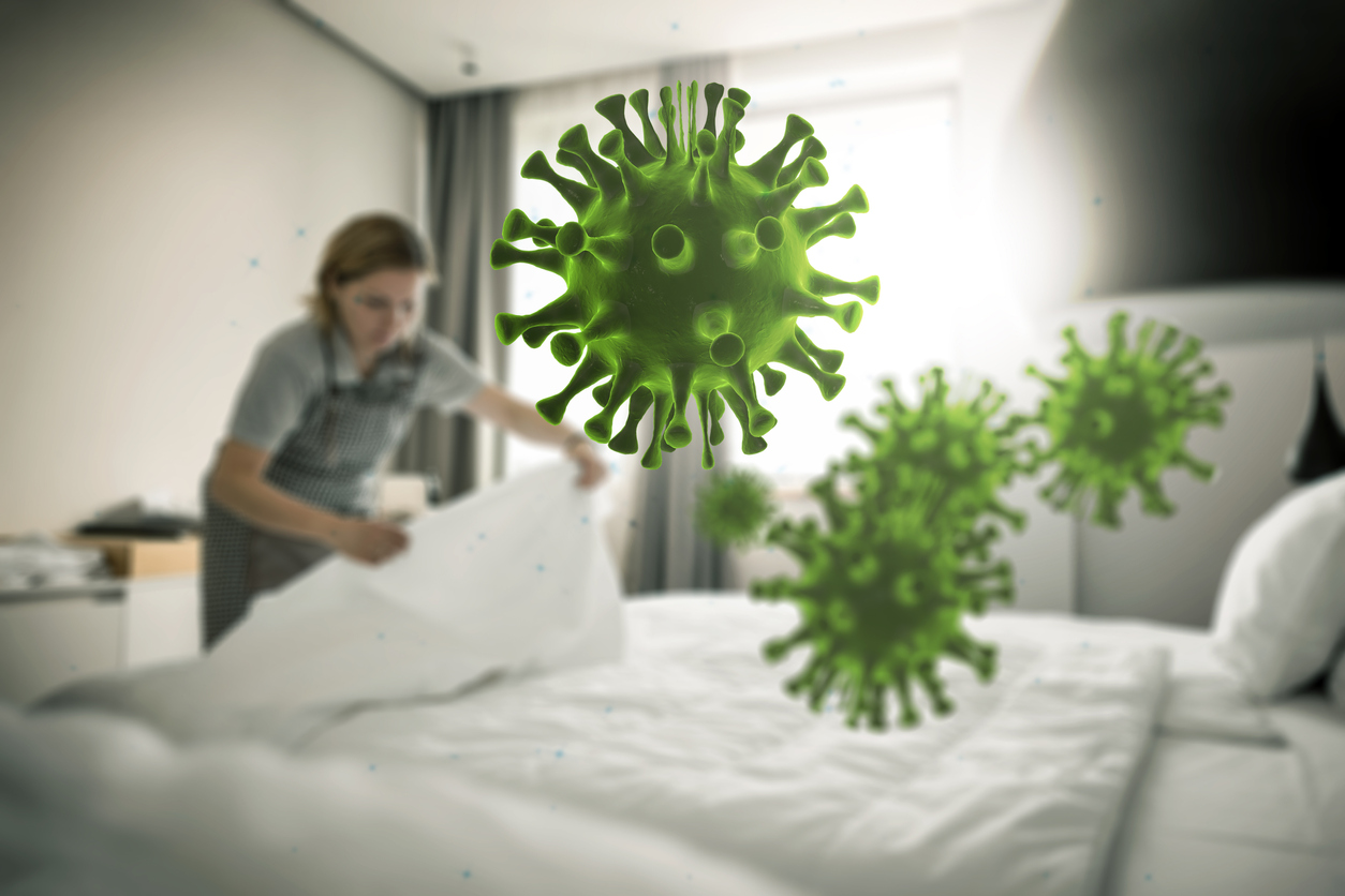 Graphic of bacteria floating in air while woman in background makes a bed