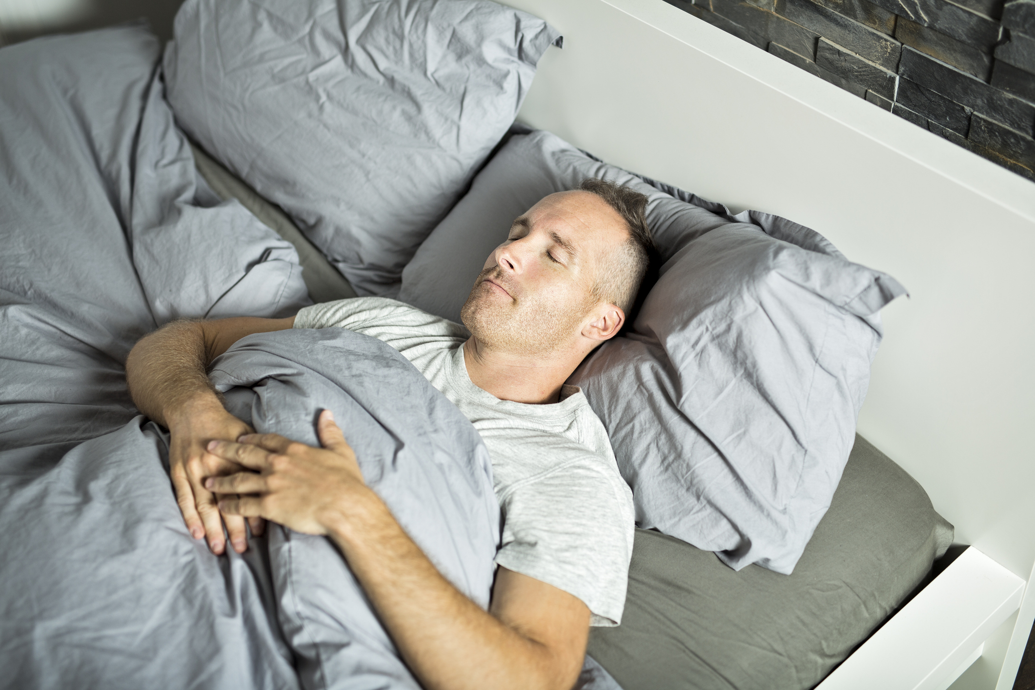 man lying on his back in bed sleeping