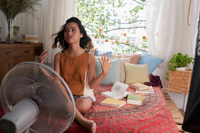 Girl cooling herself with big fan while sitting on bed.
