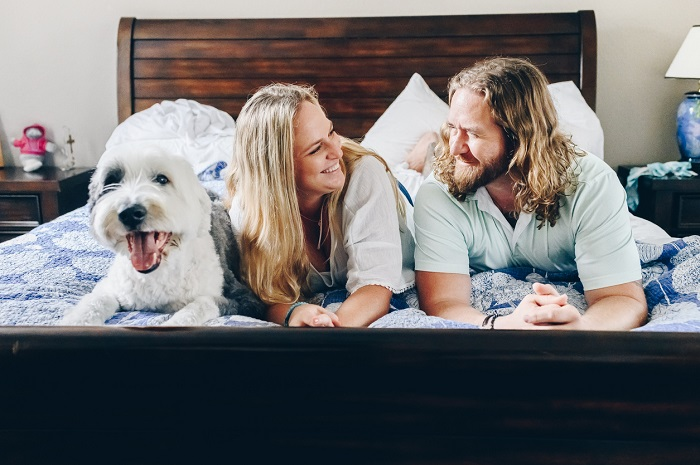 Couple lying in bed at home in their bedroom happy and smiling with their dog.