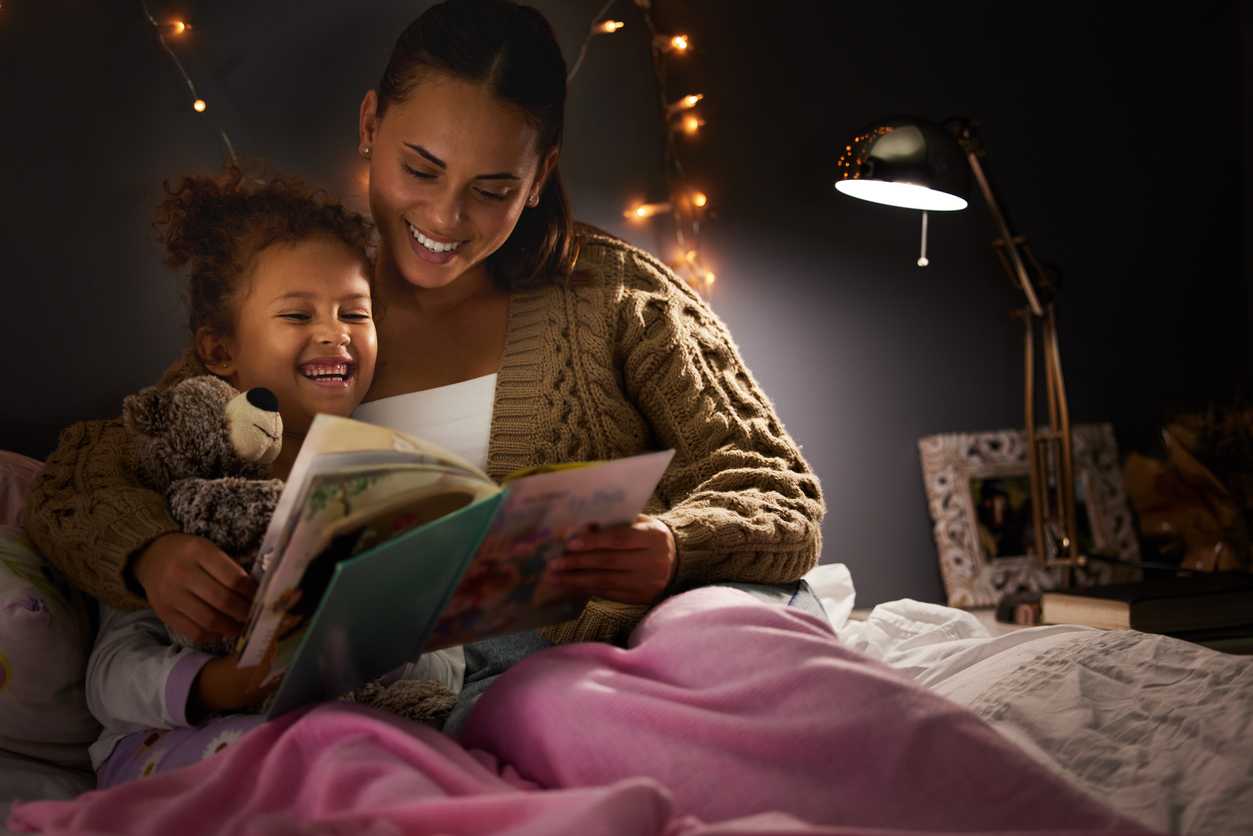 young mother reading her daughter a bedtime story