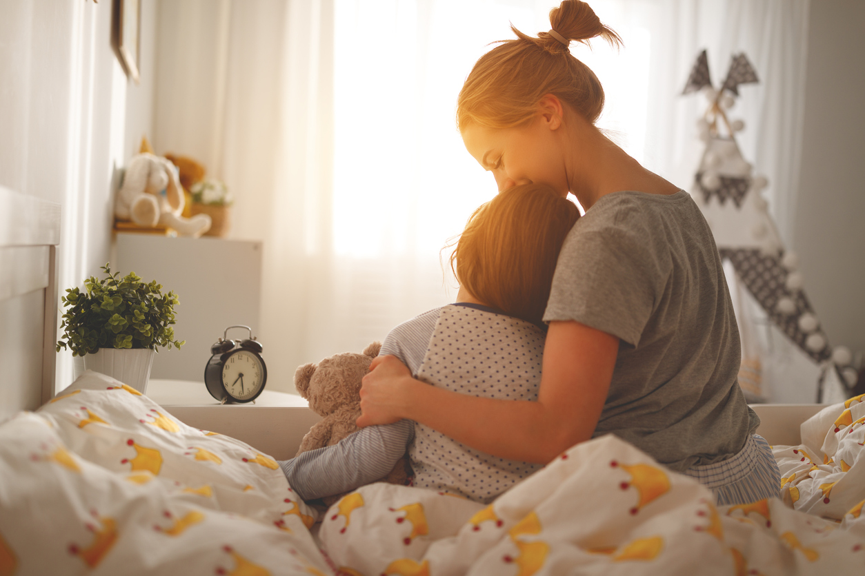 mother comforts her daughter in bed in the morning