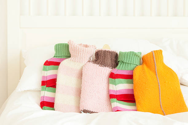 five hot water bottles in knitted covers on top of white linen