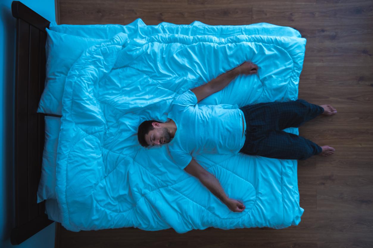 man in sleepwear lies asleep half on bed