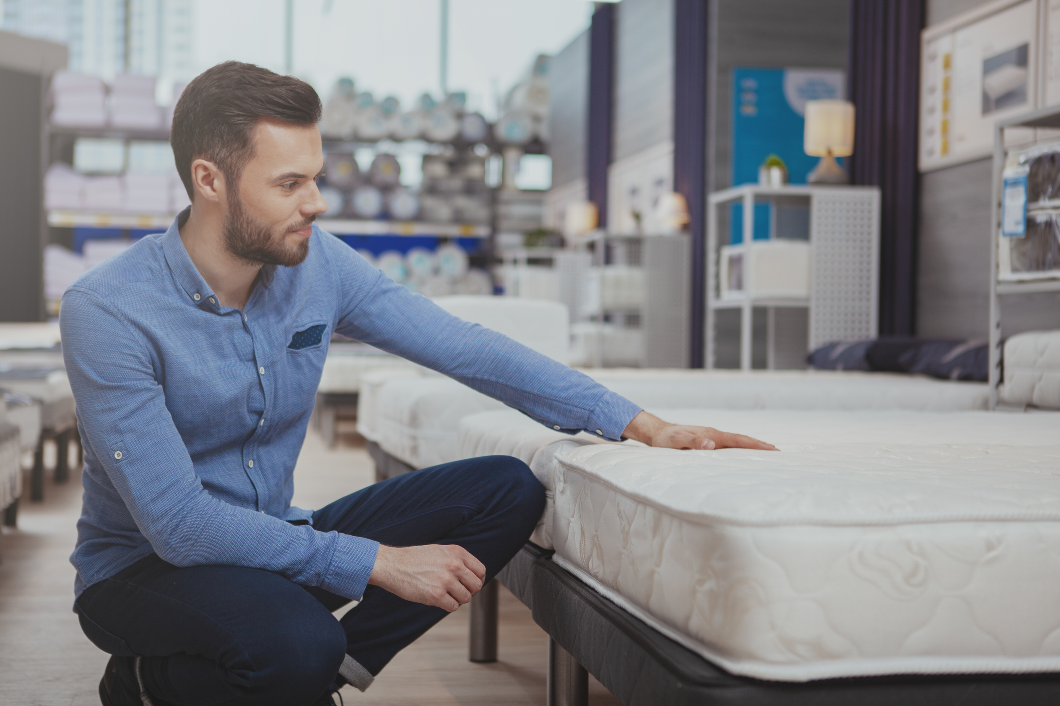man testing out a mattress in a store