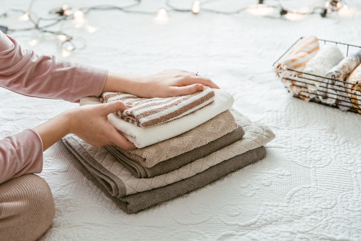 woman folding clean towels and clothes in bedroom