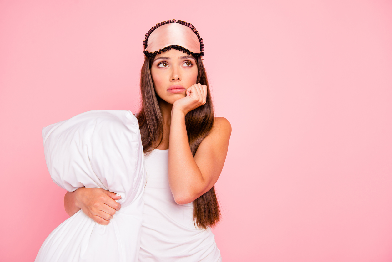 young woman holding pillow in pajamas and eye mask in front of pink background