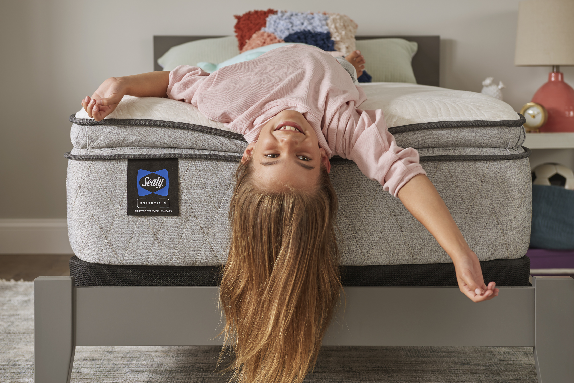 young girl hanging off the edge of a Sealy mattress