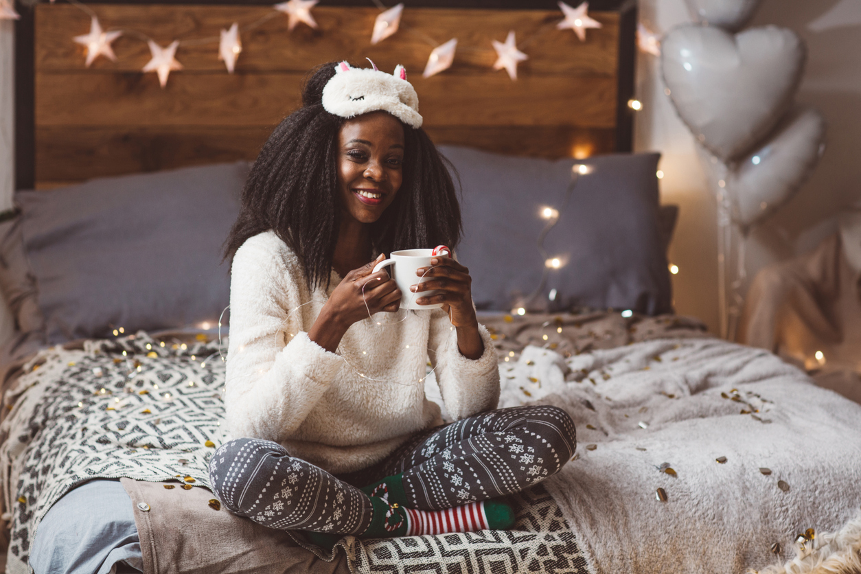 Woman sitting on her bed who's just woken up from deep sleep with a sleep mask
