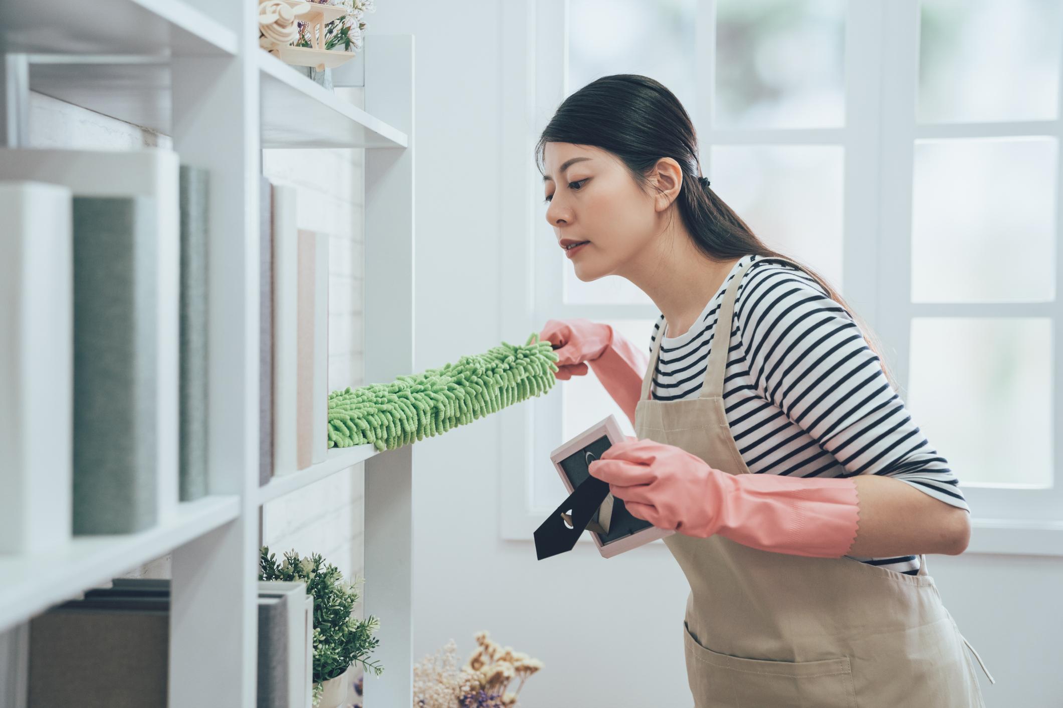 woman dusting behind the bookshelves