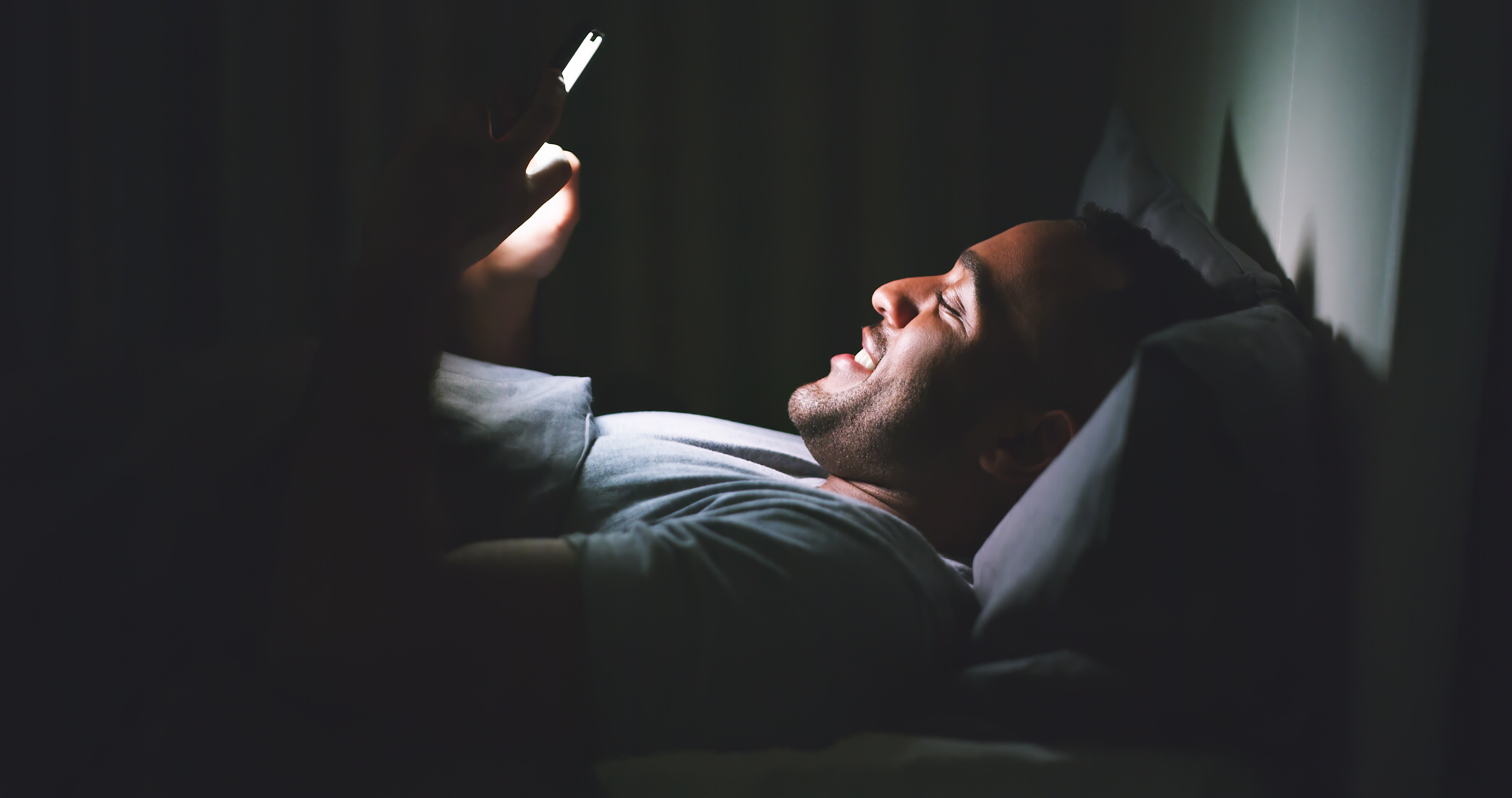 man glued to his phone a nightime