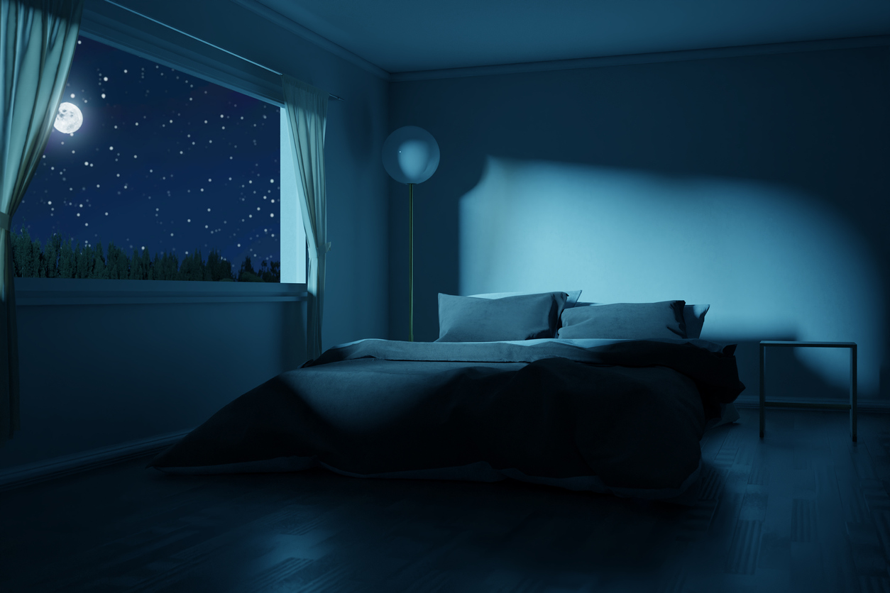 empty bed next to open with landscape of stars and moon