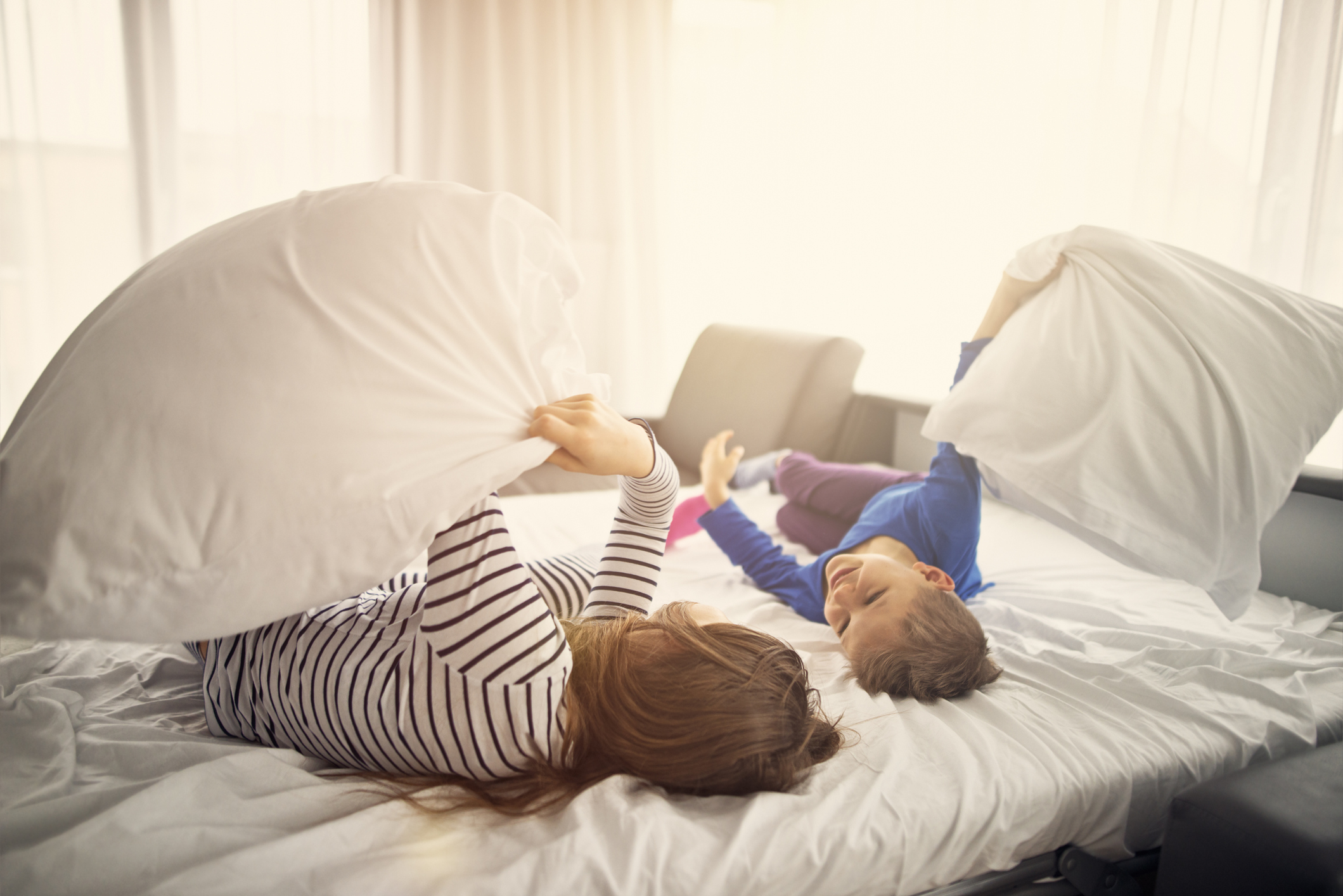 brother and sister having a pillow fight