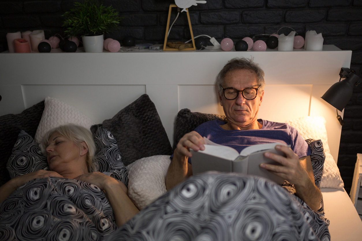 portrait of senior man reading book in bed before sleep