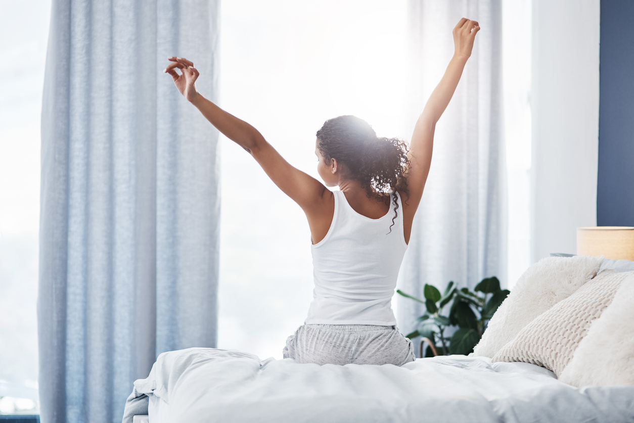 young woman stretching while sitting on her bed in the morning