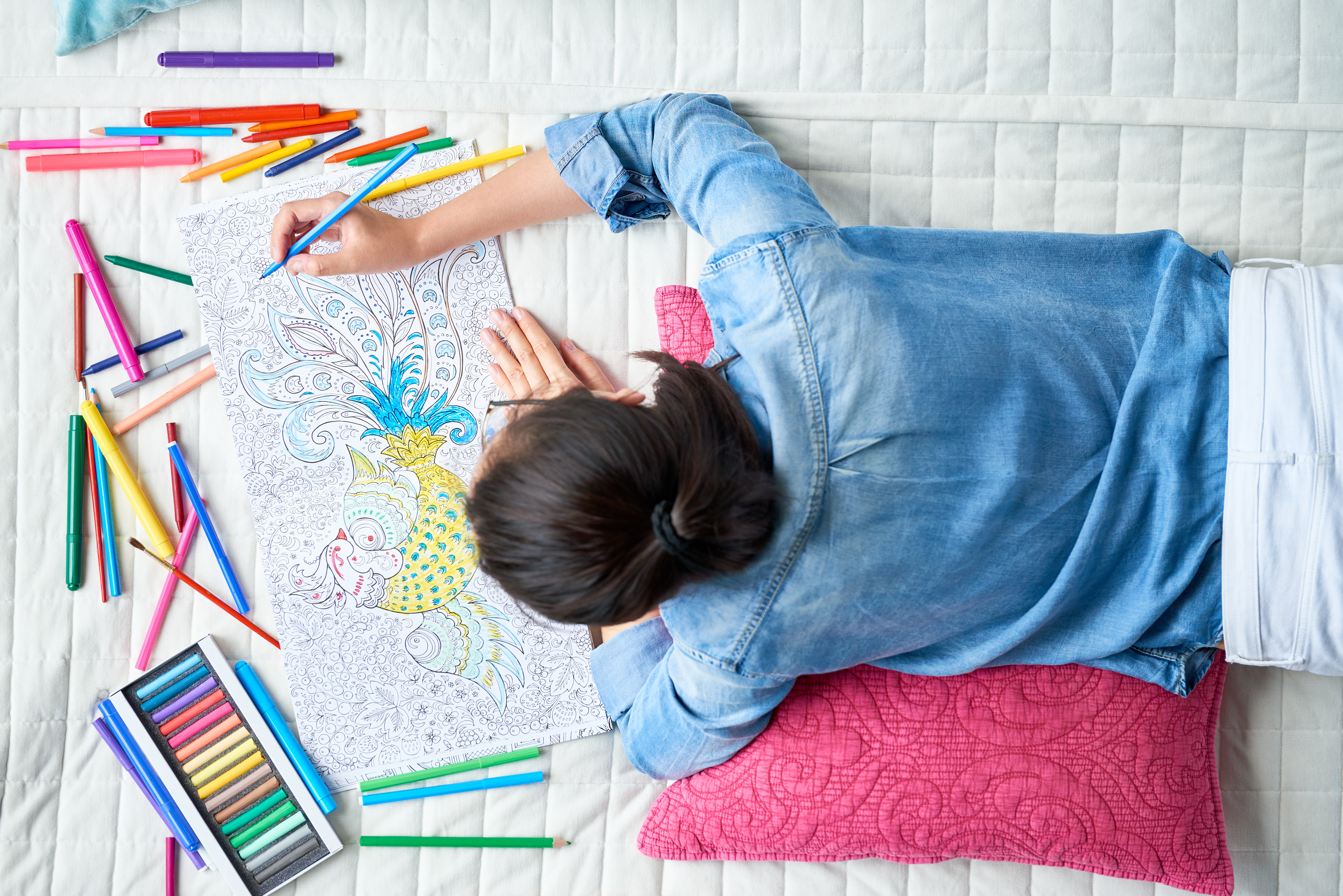 Young woman in jean jacket colors in an adult coloring book on a bed