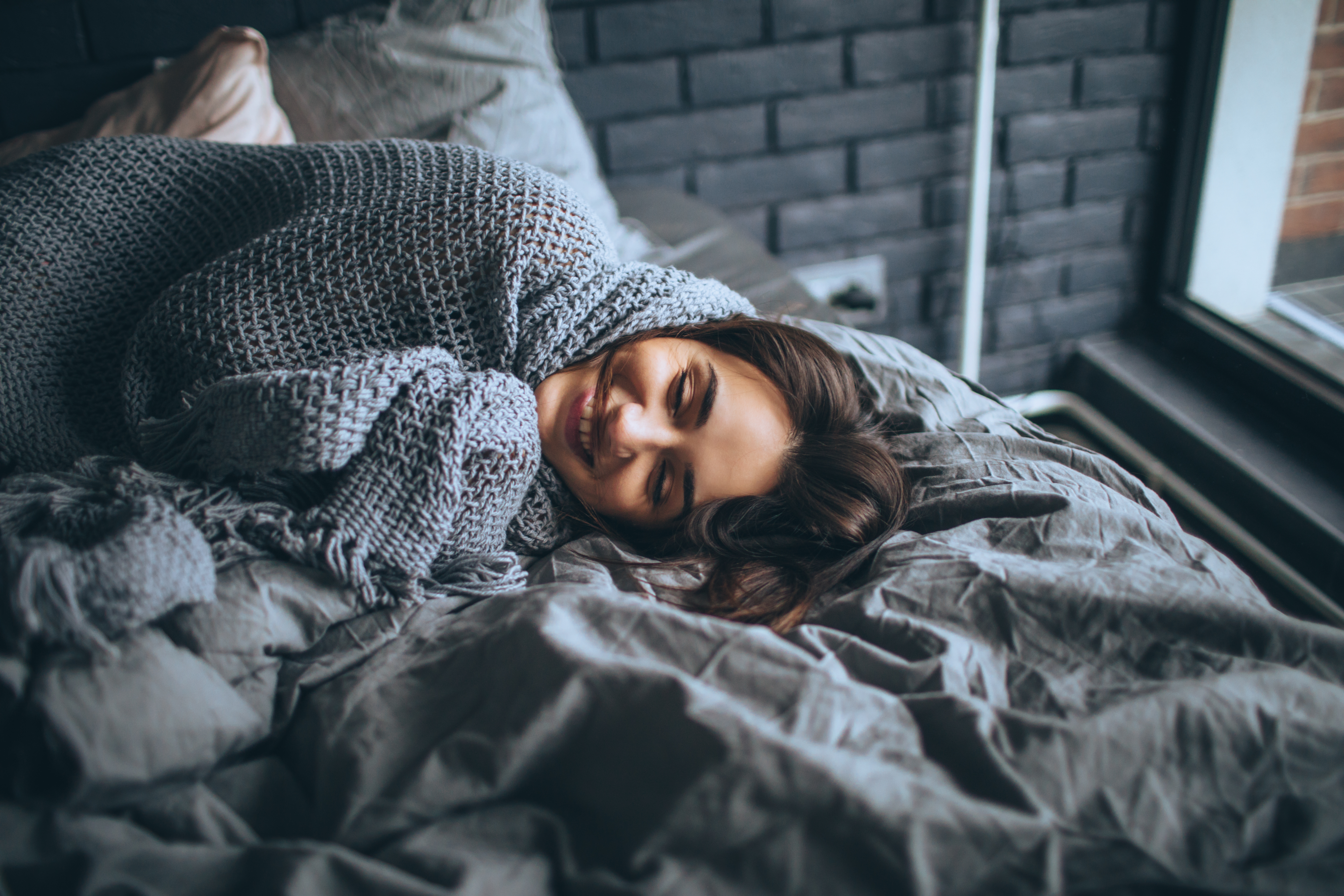 young woman smiles as she wraps herself in gray knitted throw