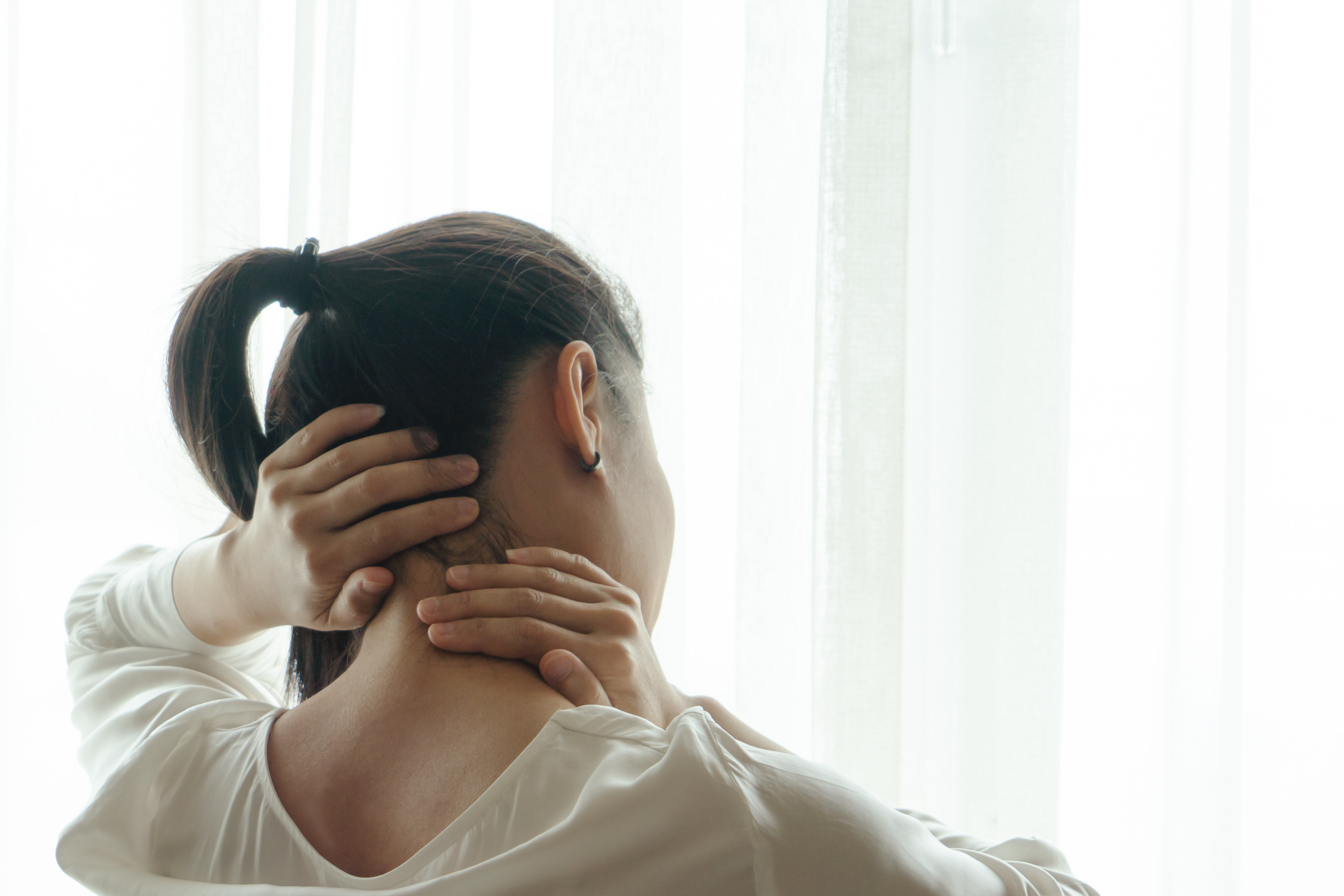 Woman with ponytail grabs the back of her neck and massages it
