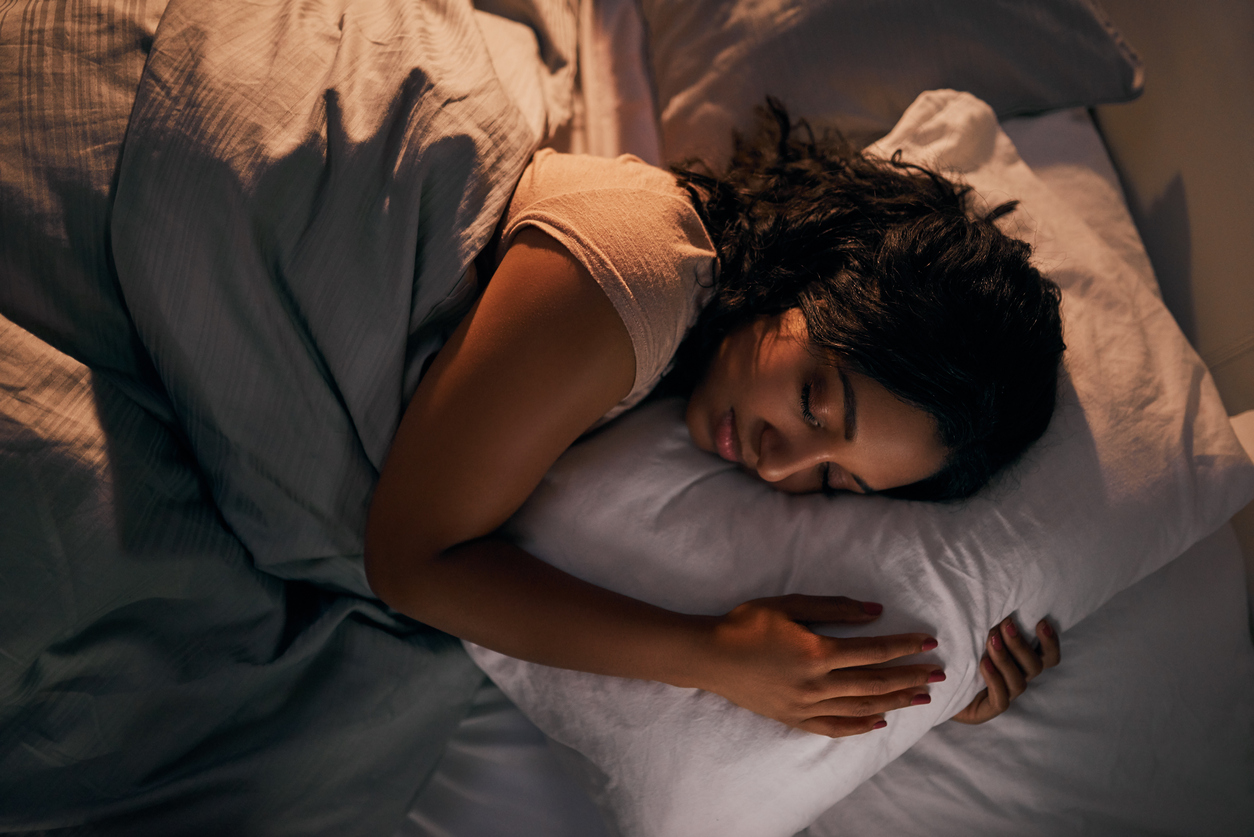 Woman sleeping in bed on her side with her a arms wrapped around a pillow