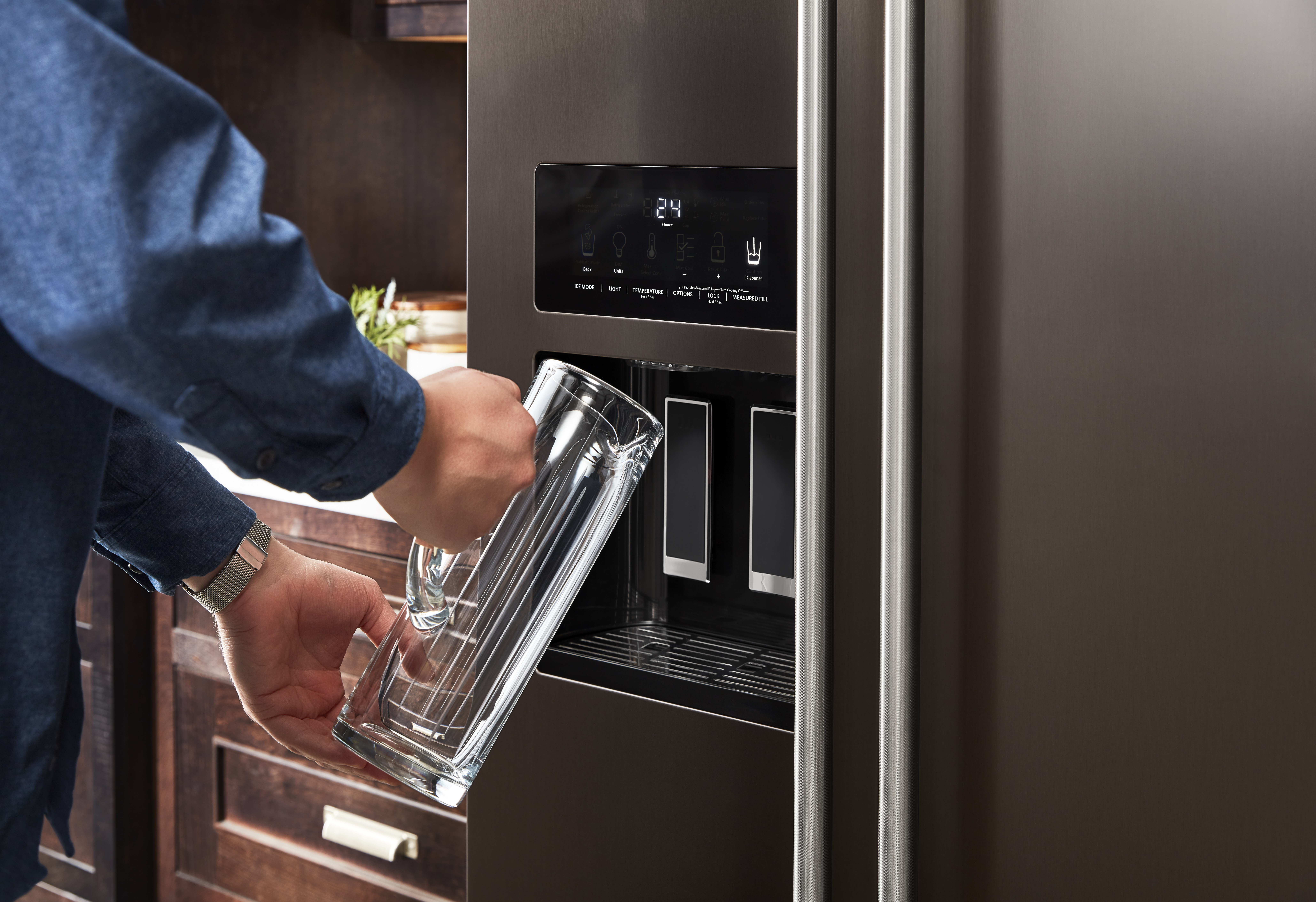 Person using water dispenser on KitchenAid krsf705hbs French door refrigerator