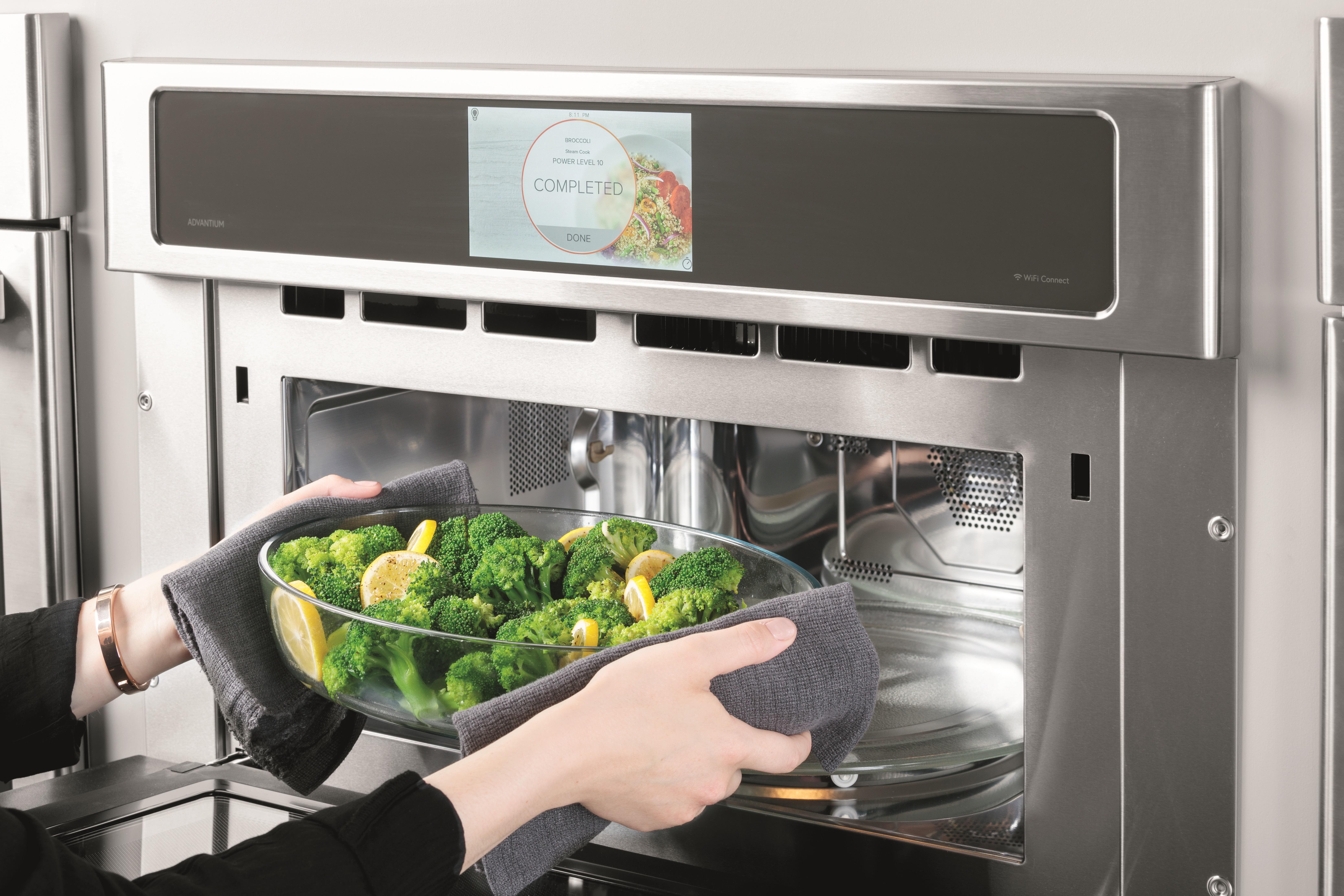 woman inserts bowl of broccoli into monogram advantium oven